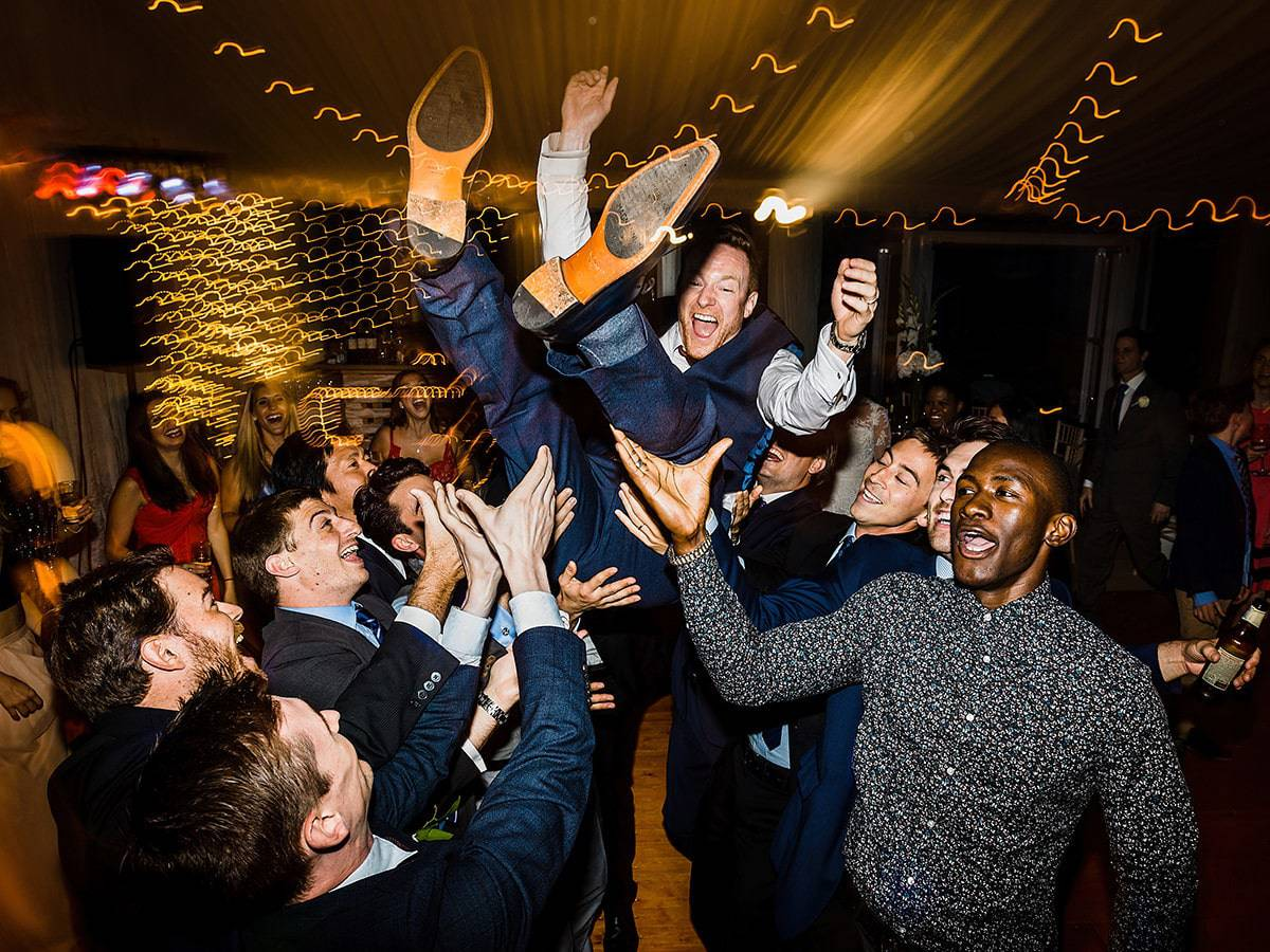groom thrown in air at wedding party andy turner photography