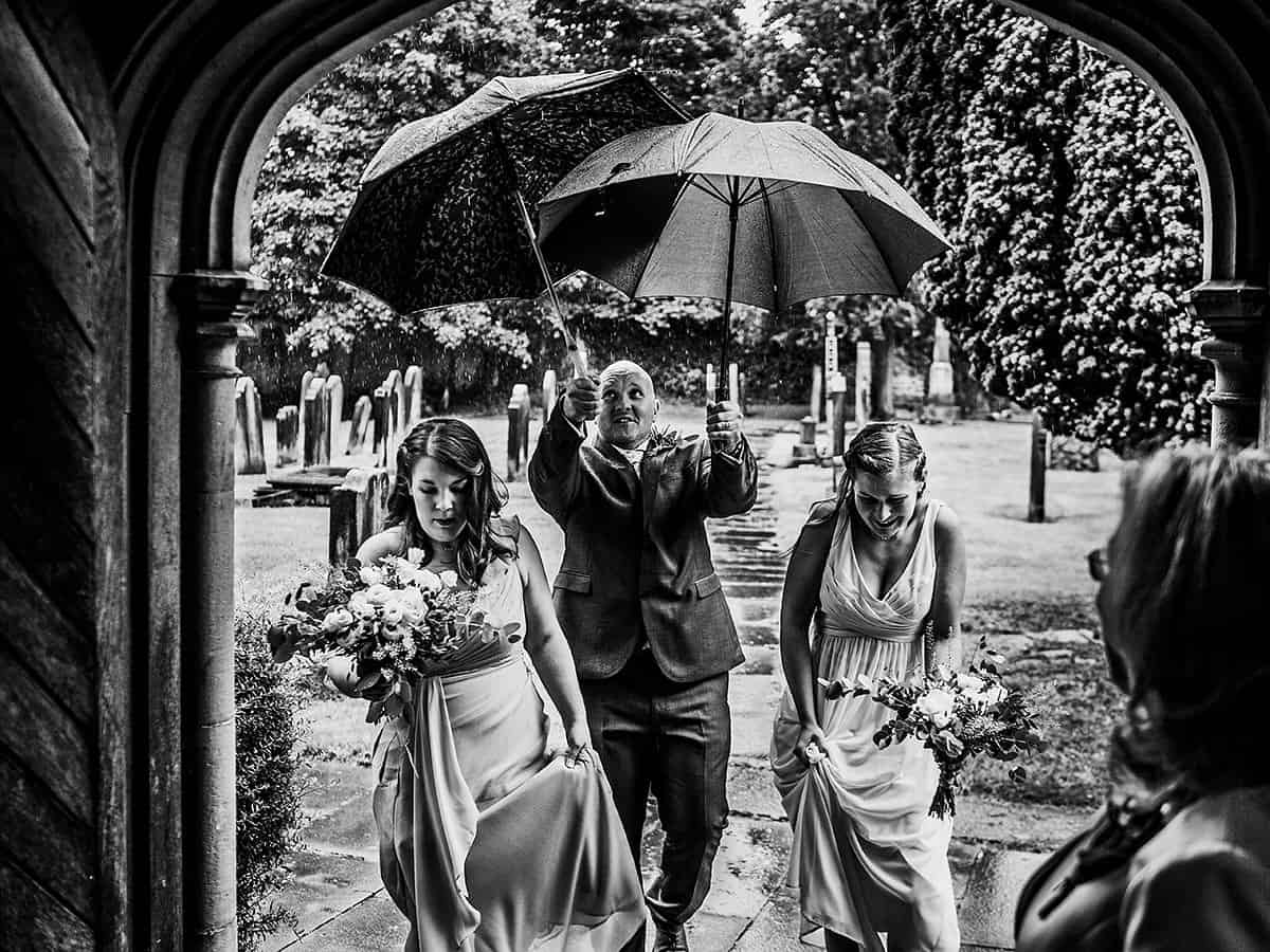 groomsman with umbrellas in the rain black and white andy turner photography